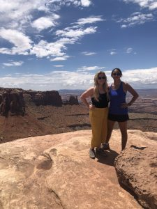 Two women standing on a desert rock formation.