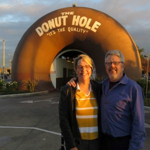 Smiling couple in front of giant donut