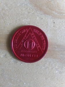 A red recovery coin with words that read: 11 month, unity, service, recovery, to thine own self be true