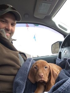 Man smiling while holding little puppy on lap.