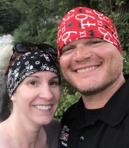 Man and woman standing outside near a waterfall, smiling.