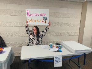 Woman holding sign that says Recovery Works.