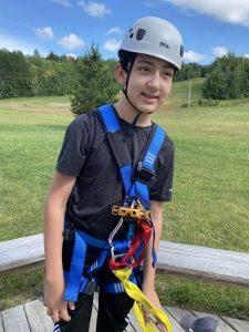 Adolescent outdoors wearing helmet and zip lining gear.