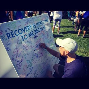 Young man writing on a board, at the Walk for Recovery, why Recovery is Important to him.