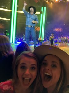 Two women, wide eyes and big smiles, near stage with Garth Brooks singing.