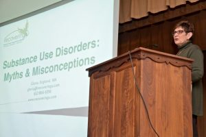 Woman speaking into microphone at podium next to a presentation on screen that reads, Substance Use Disorders: Myths & Misconceptions