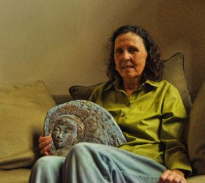 Smiling woman, sitting on couch, holding a bas-relief of an angel, created by her mother.