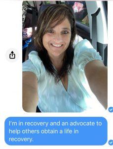 Woman smiling at cell phone camera
