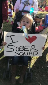 "Little girl sitting in stroller holding sign that reads, ""I heart sober squad"""