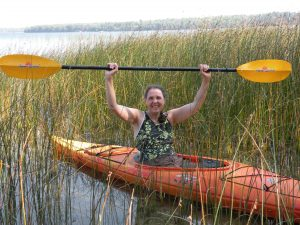Smiling woman, in kayak on lake, holding paddle above her head.
