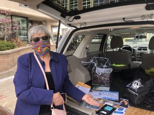Smiling woman wearing a mask and pointing to support materials in the back of a truck.