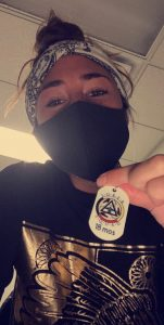 Woman wearing mask, holding necklace tag that reads, Sober Squad 18 Months