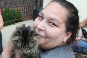 Woman holding a gray tabby cat