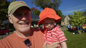 Man holding child, both wearing hats, on a sunny day outside at the Walk for Recovery
