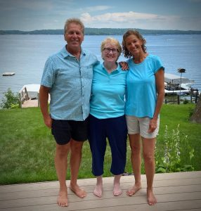 Two women and one man standing barefoot on a patio in front of a lake on a beautiful day.