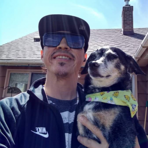 Man smiling and holding dog wearing a bandana