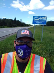 Man with mask on, standing roadside next to a sign that reads, Adopt a Highway, Sober Squad Bemidji, since 2019