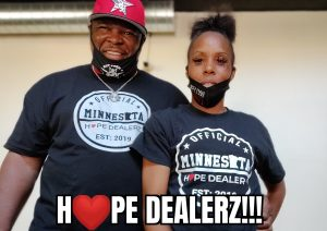 Man and woman smiling wearing Hope Dealerz t-shirts