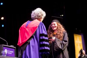 Women in college graduate robes accepting diploma.