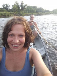 Woman and man smiling paddling in a canoe.