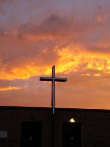 Sun rising above a church and cross