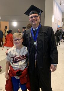 Smiling father, in college graduation cap and gown, standing arm in arm  with smiling son.