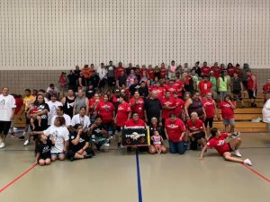 100+ smiling people, adults and children, standing close together for a community picture.