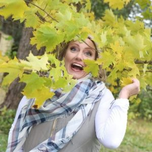 Woman smiling and laughing outside, peeking through the trees