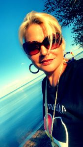 Smiling woman with sunglasses on, standing at the water's edge of Lake Mille Lacs.