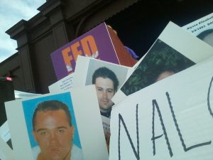 A picture of protest signs, with pictures of loved ones lost to Substance Use Disorder, at the Fed Up Rally