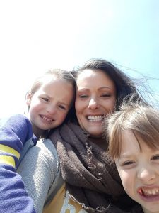 Woman and 2 children smiling with blue sky behind them