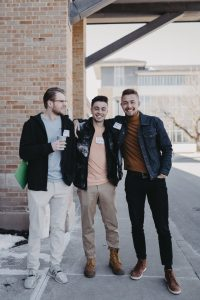Three smiling men standing arm in arm outside.