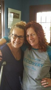 """Adult woman, with glasses, standing shoulder to shoulder in an open embrace with adult woman, wearing a shirt that says """"This is what RECOVERY looks like""""."""