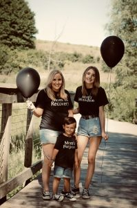 2 women and a small boy holding 2 black balloons