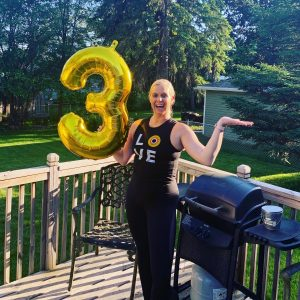 Woman holding a balloon in the shape of number 3