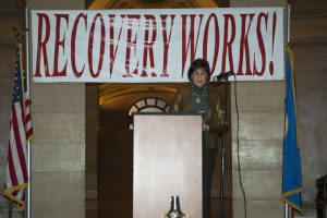 """Woman stands in the Minnesota State Capitol,  at microphone, behind podium, with sign behind her that says, """"RECOVERY WORKS"""""""