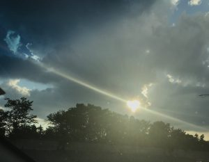 A ray of sun shining through the clouds in the shape of a heart, just above the tree line.