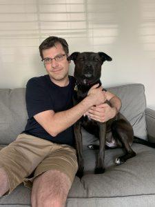Man hugging black dog