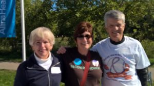 2 women and one man standing arm in arm outside at the Walk for Recovery 2015