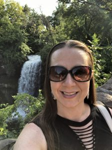 Woman wearing sunglasses and smiling in front of a waterfall