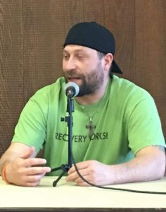 """Man seated, speaking into microphone, wearing a shirt that says, """"RECOVERY WORKS!"""""""