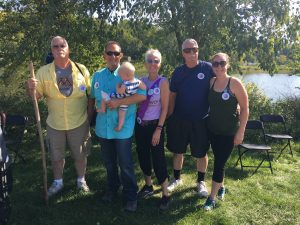 Five people, one holding a baby, standing near a lake