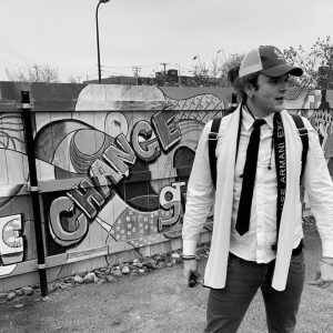 Man in front of fence covered in graffiti