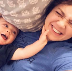 Mother laughing as toddler son touches her face.